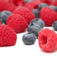 Close up view of ripe blueberry and raspberry isolated on white background